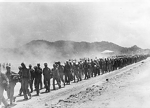 """First pictures of American war prisoners during the infamous """"March of Death"""" from Bataan to Japanese concentration camp at O'Donnell, Luzon, May 1942. Tattered column winds slowly through rugged Zambales mountains, in background. The heat and dust took its toll. These pictures were snapped by Japanese military photographer, and later seized by Filipino Guerrillas."""
